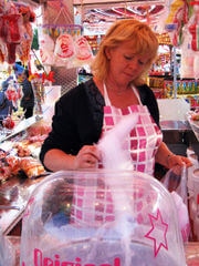 an operator spinning candy floss on the fairground