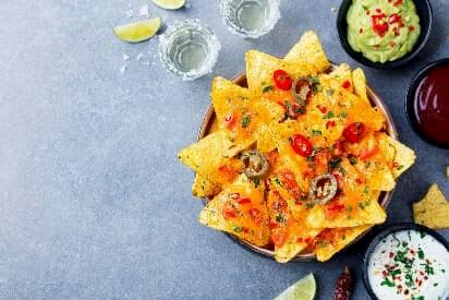 A Tray Of Mexican Nachos With Dips